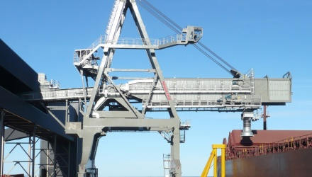 Siwertell ship loader on jetty loading iron ore into ship, blue sky